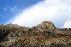 Un picco di montagna rocciosa sotto un cielo con le nuvole immagine stock