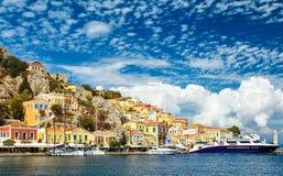 Un'piccola ed isola graziosa Simi con le sue costruzioni colourful, vicino a Rodi, la Grecia Grande vista sul dal traghetto Immagini Stock Libere da Diritti