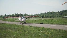 Un piccolo aereo bianco sta muovendosi lungo la pista L'elica sta filando video d archivio