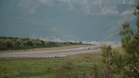 Un piccolo aereo si siede sulla pista di atterraggio sui precedenti delle montagne stock footage