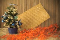 Un piccolo albero di Natale su un fondo di legno per le cartoline e Fotografia Stock Libera da Diritti