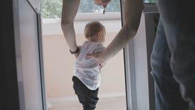 Un piccolo bambino cammina intorno all'appartamento mentre i genitori non vedono Famiglia nel paese video d archivio