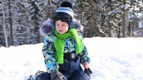 Un piccolo bambino cammina nel parco dell'inverno Bambino di gioco e sorridente su neve lanuginosa bianca Resto attivo e giochi video d archivio