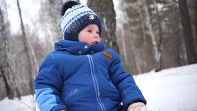 Un piccolo bambino cammina nel parco dell'inverno Un giorno di inverno pieno di sole Divertimento e giochi nell'aria fresca archivi video