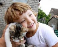 Un piccolo bambino che abbraccia un gattino Immagini Stock Libere da Diritti