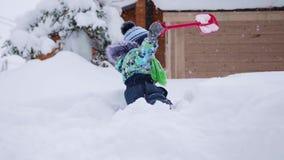 Un piccolo bambino che gioca con la neve nel parco di inverno Bambino che tiene una pala, lotti di neve nel parco Divertimento e  video d archivio