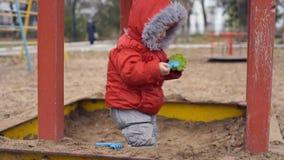 Un piccolo bambino che gioca in una sabbiera archivi video