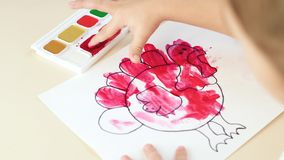 Un piccolo bambino dipinge in acquerello, trasferente la bellezza ad un foglio di carta Lo sviluppo dei bambini della scuola mate video d archivio