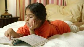 Un piccolo bambino ispano sveglio che si trova a letto gode del suo libro di esercizi di divertimento video d archivio