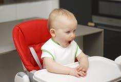 Un piccolo bambino mangia l'inceppamento ed il cereale, si siede su un seggiolone fotografia stock