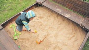 Un piccolo bambino nell'asilo che gioca nella sabbiera stock footage