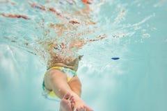 Un piccolo bambino nuota sotto l'acqua il bambino è impegnato nell'immersione con bombole fotografia stock libera da diritti