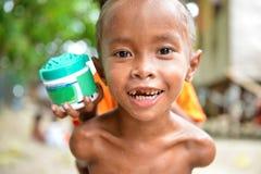 Un piccolo bambino povero che esamina macchina fotografica stranamente immagini stock