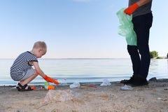Un piccolo bambino raccoglie i rifiuti sulla spiaggia Il suo papà indica il suo dito dove gettare l'immondizia I genitori insegna immagini stock libere da diritti