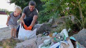 Un piccolo bambino raccoglie i rifiuti sulla spiaggia Il suo papà indica il suo dito dove gettare l'immondizia I genitori insegna stock footage