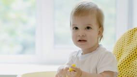Un piccolo bambino si siede su una sedia con un cucchiaio a disposizione video d archivio