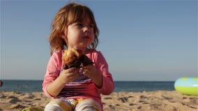 Un piccolo bambino sveglio che mangiano un bigné e le bevande innaffiano da una bottiglia Si siede sulla spiaggia contro il mare archivi video