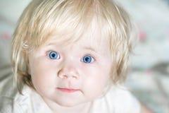 Un piccolo bambino sveglio con gli occhi azzurri fotografia stock libera da diritti