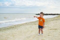 Un piccolo bambino sveglio gioca sulla spiaggia bambino sulla spiaggia vicino al mare di estate fotografia stock