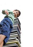 Un piccolo bambino sveglio sui libri Immagini Stock