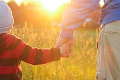 Un piccolo bambino tiene la mano di un adulto passeggiata di sera, resto unito, tempo insieme Valore familiare fotografia stock