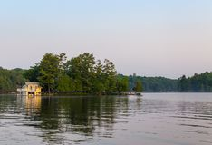 Un piccolo cottage della riva del lago su un'isola nel Muskokas, Ontario, ad alba immagini stock