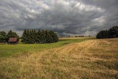 Un piccolo cottage su un prato e un campo raccolto prima della tempesta Immagini Stock