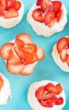 Un piccolo dessert di Pavlova della meringa con alcune fette della fragola su un fondo blu Vista superiore immagine stock