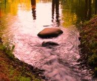 Un piccolo fiume bianco-morbido che investe le rocce fotografia stock