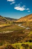 Un piccolo fiume che passa una valle della montagna immagini stock