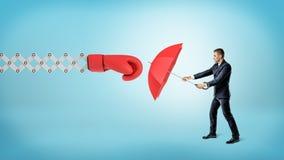 Un piccolo imprenditore che tiene un ombrello rosso per nascondersi da un grande guantone da pugile su un braccio della molla fotografie stock