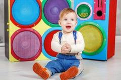 Un piccolo infante si siede sul pavimento e ride Childho di concezione Fotografie Stock