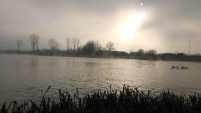 Un piccolo lago durante l'inverno e un'alba fotografie stock