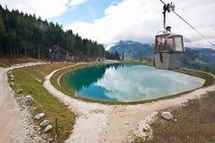 Un piccolo lago nelle montagne e nell'ascensore di sci Fotografia Stock