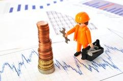 Un piccolo lavoratore ad una piramide delle monete Immagini Stock Libere da Diritti