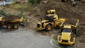 Un piccolo modello dell'escavatore carica l'argilla in un autocarro con cassone ribaltabile archivi video