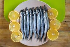 Un piccolo pesce con le fette rotonde di bugia del limone in un piatto su una tavola di legno immagini stock