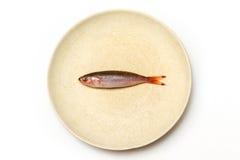 Un piccolo pesce sul piatto bianco Fotografia Stock Libera da Diritti