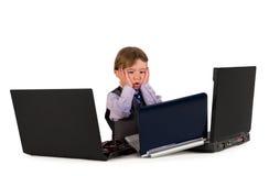 Un piccolo ragazzino che lavora ai computer portatili. Fotografia Stock