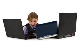 Un piccolo ragazzino che lavora ai computer portatili. Fotografie Stock Libere da Diritti