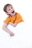 Un piccolo ragazzo felice che tiene una scheda in bianco Immagini Stock