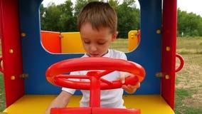 Un piccolo ragazzo felice si siede in un'automobile di legno del giocattolo e gira il volante playground archivi video