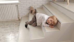 Un piccolo ragazzo sveglio che si trova sui punti in un appartamento alla moda luminoso archivi video