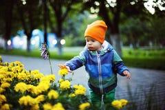 Un piccolo ragazzo sveglio del bambino sta sforzando le mani verso i fiori Immagini Stock
