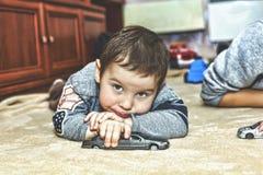 Un piccolo ragazzo triste con uno sguardo pensieroso Ragazzino che gioca le automobili del giocattolo a casa sul tappeto fotografia stock