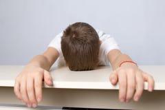 Un piccolo scolaro è caduto addormentato Situazione di sforzo immagine stock