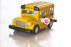 Un piccolo scuolabus del giocattolo sopra bianco Fotografie Stock