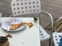 Un piccolo uccello, un passero mangia una pizza deliziosa da una tavola in un caffè all'aperto sulla via Immagini Stock