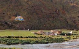 Un piccolo villaggio con l'alta montagna nella parte anteriore Immagini Stock