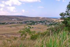 Un piccolo villaggio nella pianura di una collina con erba secca intorno e un mare che è visibile nella distanza Fotografia Stock Libera da Diritti